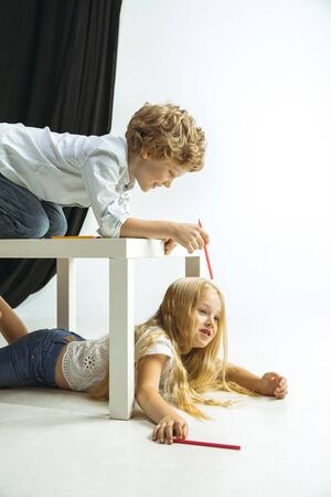 Boy and girl preparing for school after a long summer break. Back to school. Little caucasian models playing together on studio background. Childhood, education, holidays or homework concept.