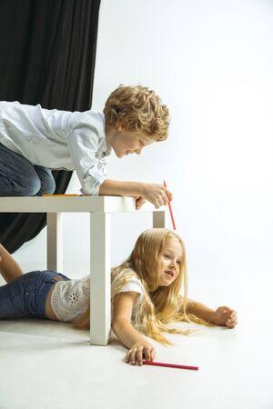 Niño y niña preparándose para la escuela después de un largo receso de verano. De vuelta a la escuela. Pequeños modelos caucásicos jugando juntos en el fondo del estudio. Concepto de infancia, educación, vacaciones o deberes.