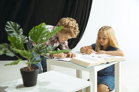 Boy and girl preparing for school after a long summer break. Back to school. Little caucasian models making homework together on studio background. Childhood, education, holidays or homework concept. 免版税图像