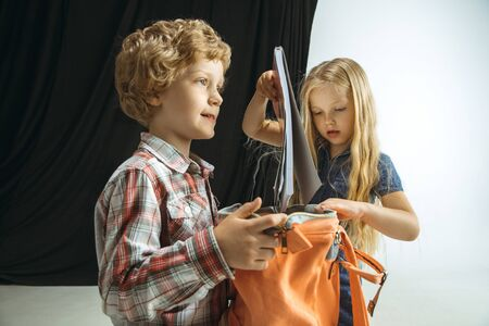 Boy and girl preparing for school after a long summer break. Back to school. Little caucasian models packing a bag together on studio background. Childhood, education, holidays or homework concept.