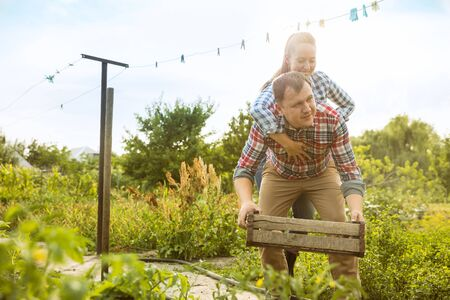 Young and happy farmers couple at their garden in sunny day. Man and woman engaged in the cultivation of eco friendly products. Concept of farming, agriculture, healthy lifestyle, family occupation. Reklamní fotografie