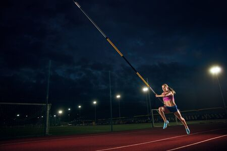 Ready to overcome difficulties. Professional female pole vaulter training at the stadium in the evening. Practicing outdoors. Concept of sport, activity, healthy lifestyle, action, movement, motion.