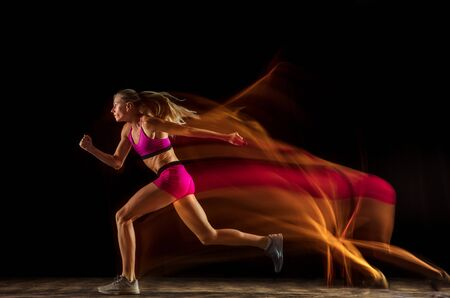 Professional female relay racer training isolated on black studio background in mixed light. Woman in sportsuit practicing in running. Healthy lifestyle, sport, workout, motion, action concept. Banco de Imagens