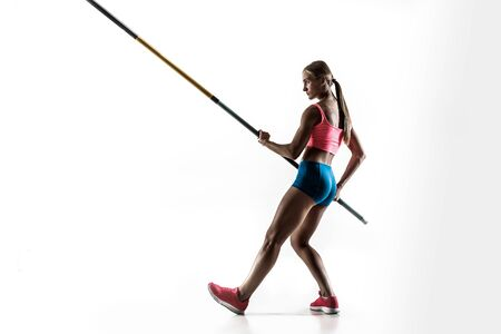 Power and beauty and purity. Professional female pole vaulter training on white studio background. Fit and slim female model practicing. Concept of sport, healthy lifestyle, action, movement, motion.