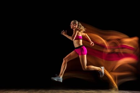 Professional female relay racer training isolated on black studio background in mixed light. Woman in sportsuit practicing in running. Healthy lifestyle, sport, workout, motion, action concept. Standard-Bild