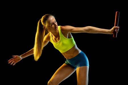 Professional female relay racer training isolated on black studio background in neon light. Woman in sportsuit practicing in running. Healthy lifestyle, sport, workout, motion, action concept. Archivio Fotografico