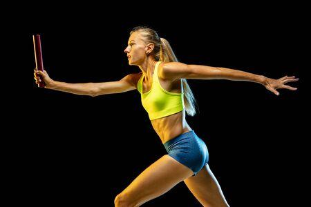 Professionelles weibliches Staffellauftraining isoliert auf schwarzem Studiohintergrund im Neonlicht. Frau im Sportanzug, die beim Laufen übt. Gesunder Lebensstil, Sport, Training, Bewegung, Aktionskonzept. Standard-Bild