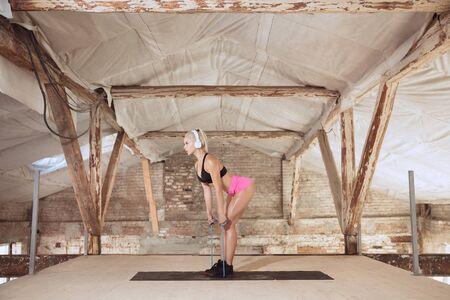Una giovane donna atletica in cuffie bianche che si allena ascoltando la musica in un cantiere abbandonato. Esercizio con la corda. Concetto di stile di vita sano, sport, attività, perdita di peso.