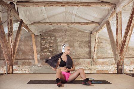Una joven mujer atlética en auriculares blancos trabajando escuchando música en un sitio de construcción abandonado. Descansando después del entrenamiento. Concepto de estilo de vida saludable, deporte, actividad, pérdida de peso. Foto de archivo