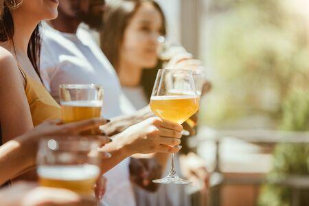 Giovane gruppo di amici che bevono birra, si divertono, ridono e festeggiano insieme. Donne e uomini con bicchieri di birra in una giornata di sole. Oktoberfest, amicizia, solidarietà, felicità, concetto estivo. Archivio Fotografico
