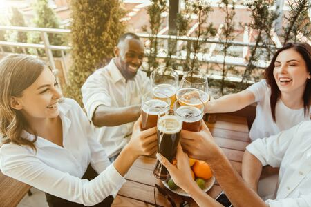 Young group of friends drinking beer, having fun, laughting and celebrating together. Women and men with beers glasses in sunny day. Oktoberfest, friendship, togetherness, happiness, summer concept.
