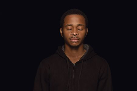 Close up portrait of young african-american man isolated on black studio background. Real emotions of male model with eyes closed, looks calm. Facial expression, human nature and emotions concept. Stock Photo