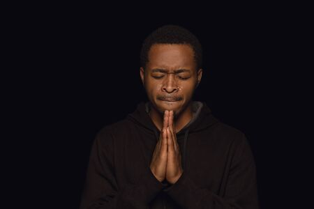 Close up portrait of young african-american man isolated on black studio background. Photoshot of real emotions of male model. Praying and crying. Facial expression, human nature and emotions concept. Stock Photo