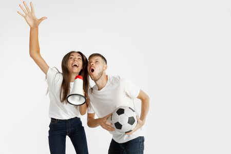 Portrait of beautiful young couple football or soccer fans on white studio background. Facial expression, human emotions, advertising, sport concept. Woman and man jumping, screaming, having fun.