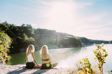 Young lesbians couple having fun at riverside in sunny day. Beautiful women exercizing yoga together on the nature. Concept of relationship, love, summer, weekend, honeymoon, healthy lifestyle.