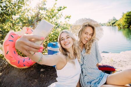 Young lesbians couple having fun at riverside in sunny day. Women spending time on the nature together. Drinking wine, making selfie. Concept of relationship, love, summer, weekend, honeymoon.