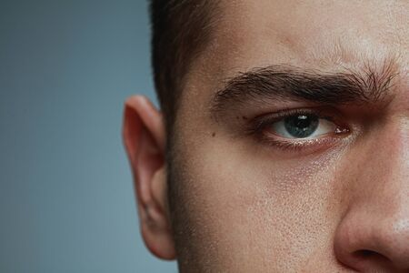 Close-up portrait of young man isolated on grey studio background. Caucasian male models face and blue eye. Concept of mens health and beauty, self-care, body and skin care, medicine or phycology.