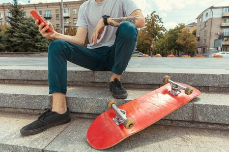 Skateboarder resting after riding at the citys street in sunny day. Young man in sneakers and cap with a longboard on the asphalt. Concept of leisure activity, sport, extreme, hobby and motion.