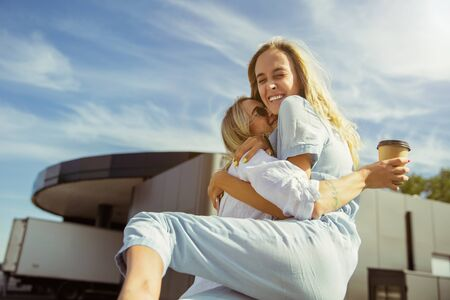 Young lesbians couple preparing for vacation trip on the car in sunny day. Cuddling and drinking coffee before going to sea or ocean. Concept of relationship, love, summer, weekend, honeymoon.