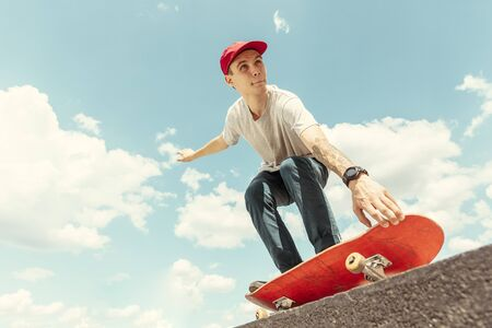 Skateboarder doing a trick at the citys street in sunny day. Young man in sneakers and cap riding and longboarding on the asphalt. Concept of leisure activity, sport, extreme, hobby and motion.