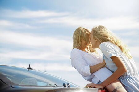 The young lesbians couple broke down the car while traveling on the way to rest. Kissing and cuddling on the cars trunk. Relationship, troubles on the road, vacation, holidays, honeymoon concept. Stock Photo