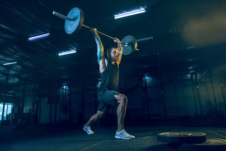Young healthy man athlete doing exercise with the barbell in the gym. Single male model training hard and practicing in lunges. Concept of healthy lifestyle, sport, fitness, bodybuilding, crossfit.
