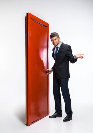 Knocking in emptiness. Young man in black suit trying to open the red door in career ladder, but its closed. No way for motivation. Concept of office workers troubles, business, problems, stress.