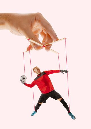 Man like a puppet in somebodies hands on pink background. Concept of unfair manipulation, phycology of exploitation, mental technique, motivation. Puppets and their masters. Possessive relationship.