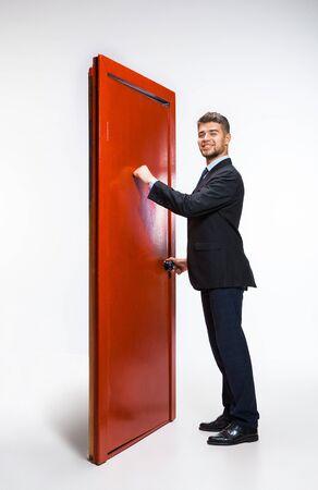Frapper dans le vide. Jeune homme en costume noir essayant d'ouvrir la porte rouge dans l'échelle de carrière, mais c'est fermé. Pas moyen de se motiver. Concept de problèmes d'employés de bureau, d'affaires, de problèmes, de stress. Banque d'images