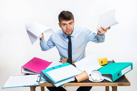 The young man has a complete mess in the workplace, he cannot organize his space and find important documents. Concept of office workers troubles, business, advertising, everyday problems. Reklamní fotografie