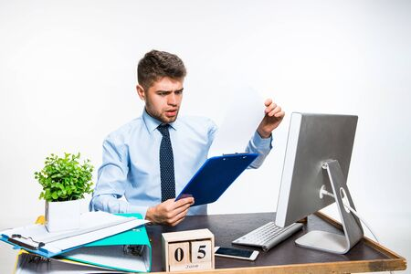 The young man getting awful, shocking message. Cant believe his eyes, loses his balance in shock, getting upset and angry. Concept of office workers troubles, business, information problems.