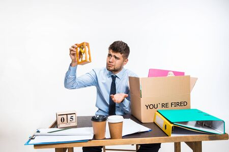 The young man is fired and folds things in the workplace, folders, documents. Couldnt cope with responsibilities. Concept of office workers troubles, business, advertising, resignation problems.