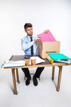 The young man is resigned and folds things in the workplace, folders, documents. Couldnt cope with responsibilities. Concept of office workers troubles, business, advertising, resignation problems. Stock Photo