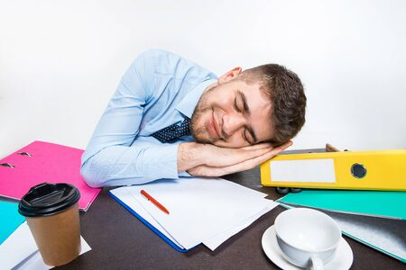 The young man is brazenly sleeping on the desktop during his working hours. Can not cope with responsibilities. Concept of office workers troubles, business, advertising, everyday problems. Banco de Imagens