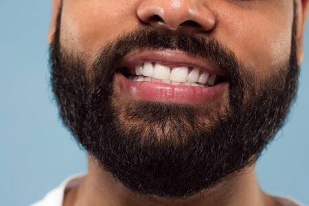 Close up portrait of young hindoo mans face with beard, white teeth and lips on blue background. Smiling. Human emotions, facial expression, advertising concept. Negative space.