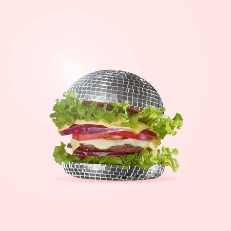 Food as fast as a disco dance. A burger as an discoball with salad, potato and meat. Negative space to insert your text. Modern design. Contemporary art collage. An alternative view of street food. Stock Photo
