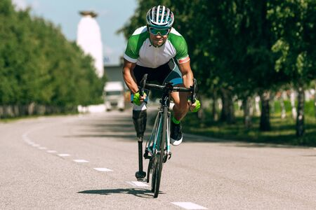 Athlete with disabilities or amputee training in cycling in sunny summers day. Professional male sportsman with leg prosthesis practicing outdoors. Disabled sport and healthy lifestyle concept.