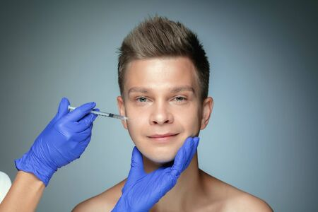 Close-up portrait of young man isolated on grey studio background. Filling surgery procedure, lips and cheekbones. Concept of mens health and beauty, cosmetology, body and skin care. Anti-aging.