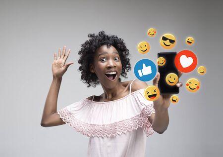Interacciones de redes sociales en el teléfono móvil. Marketing digital en Internet, chatear, comentar, gustar. Sonrisas e iconos sobre la pantalla del teléfono inteligente, que se sostiene por una mujer joven sobre fondo gris de estudio.