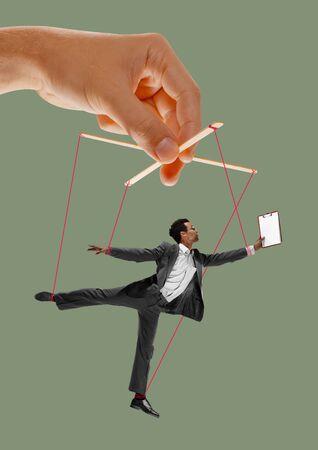 L'homme comme une marionnette dans les mains de quelqu'un sur fond vert. Concept de manipulation déloyale, phycologie de l'exploitation, technique mentale, motivation. Marionnettes et leurs maîtres. Relation possessive.
