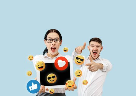 Social media interactions on mobile phone. Internet digital marketing, Chating, commenting, liking. Smiles and icons above tablet screen, that holding by young couple on blue studio background.
