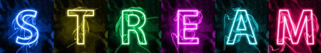 Social medias interactions in colorful neon light. Internet digital marketing, modern mass medias term. Sign against dark background. Stylized colorful letters of STREAM banner. Stock Photo