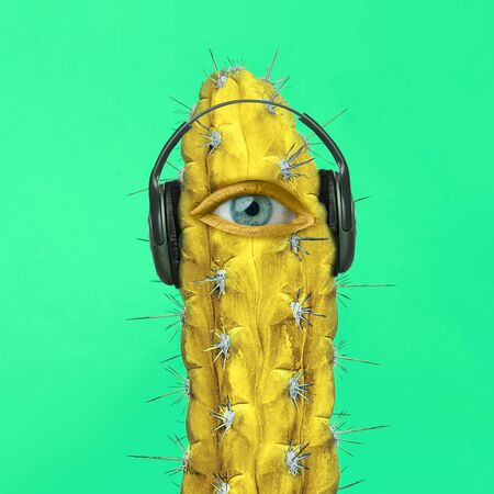 Dance mood. Cactus with a human eye is listening to music in headphones on green background. Negative space. Modern design. Contemporary art. Creative conceptual and colorful collage.