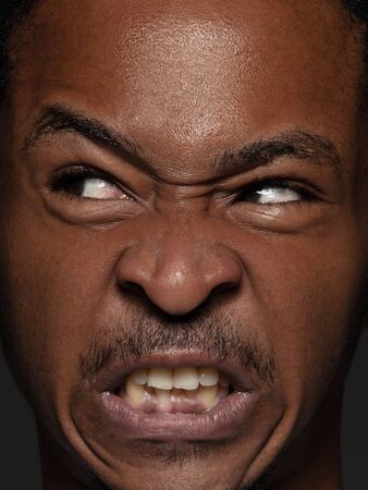 Close up portrait of young and emotional african-american man. Highly detail photoshot of male model with well-kept skin and bright facial expression. Concept of human emotions. Angry, agressive.