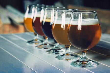 Vasos de diferentes tipos de cerveza oscura y clara en la mesa de madera en línea. Se preparan deliciosas bebidas frías para una gran fiesta de amigos. Concepto de bebidas, diversión, reunión, oktoberfest. Foto de archivo
