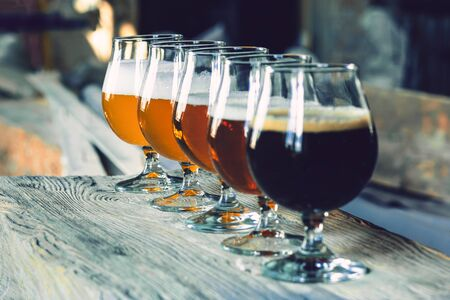 Glasses of different kinds of dark and light beer on wooden table in line. Cold delicious drinks are prepared for a big friends party. Concept of drinks, fun, meeting, oktoberfest. Stockfoto