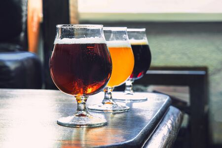 Glasses of different kinds of dark and light beer on wooden table in line. Cold delicious drinks are prepared for a big friends party. Concept of drinks, fun, meeting, oktoberfest. 스톡 콘텐츠