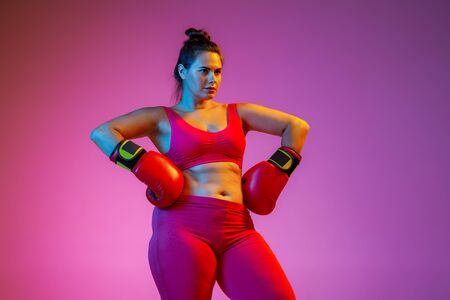 Young caucasian plus size female models doing exercises on gradient purple background in neon light. Active boxing in gloves. Concept of sport, healthy lifestyle, body positive, equality.