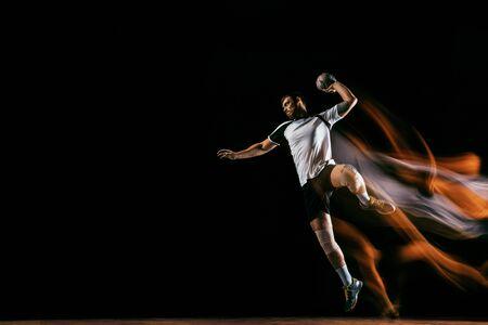 Jugador de balonmano joven caucásico en acción y movimiento en luces mixtas sobre fondo negro de estudio. Ajuste deportista profesional masculino. Concepto de deporte, movimiento, energía, estilo de vida dinámico y saludable.