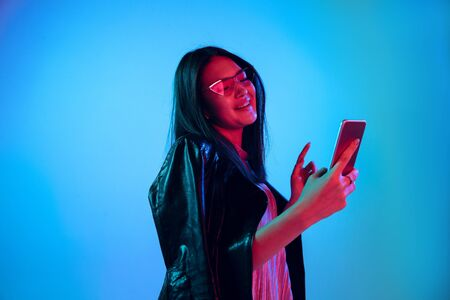 Beautiful female half-length portrait isolated on blue studio background in neon light. Young emotional woman. Human emotions, facial expression concept. Using smartphone and wireless headphones.